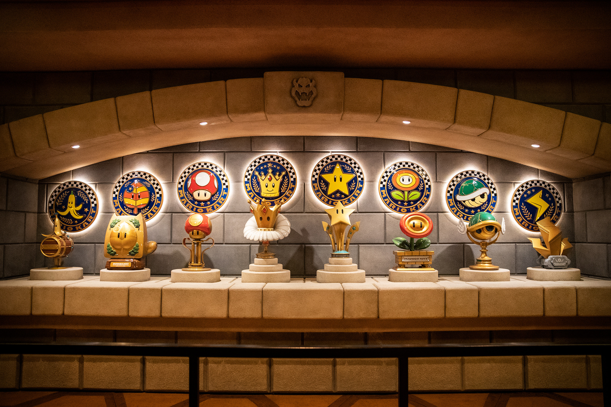 Detail of trophy case showcasing both medallions and trophies from the Mario Kart series. Photo credit: Universal and Nintendo